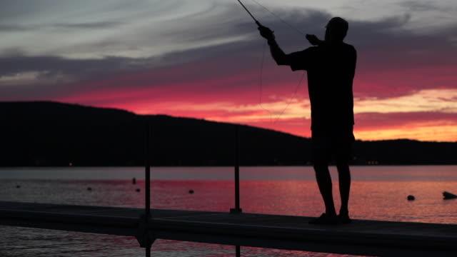 vídeos y material grabado en eventos de stock de cinemagraph de hombre pescador al atardecer - caña de pescar