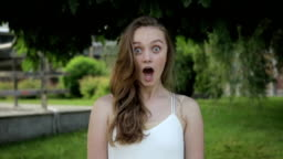 Cinemagraph of pretty cute young woman surprised shocked on green trees background. Loopable