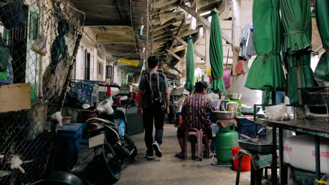 cinemagraph of senior woman sitting in market with young man. - asian market stock videos and b-roll footage