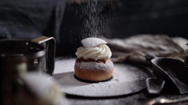 cinemagraph of sugar falling on a traditional swedish semla dessert - swedish culture stock videos & royalty-free footage