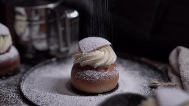 filmgraf av socker som faller på en traditionell svensk semladessert - cinemagrafi bildbanksvideor och videomaterial från bakom kulisserna