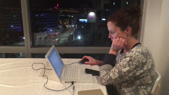 cinemagraph of upset woman works late at night from home - hand am kinn stock-videos und b-roll-filmmaterial