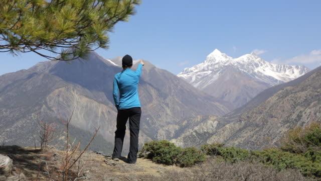 vídeos de stock, filmes e b-roll de cinemagraph de mulher alpinista caminhadas em torno de trek annapurna, no nepal - himalaias