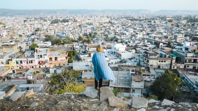 cinemagraph of young woman looking off to cityscape - rajasthan stock videos and b-roll footage