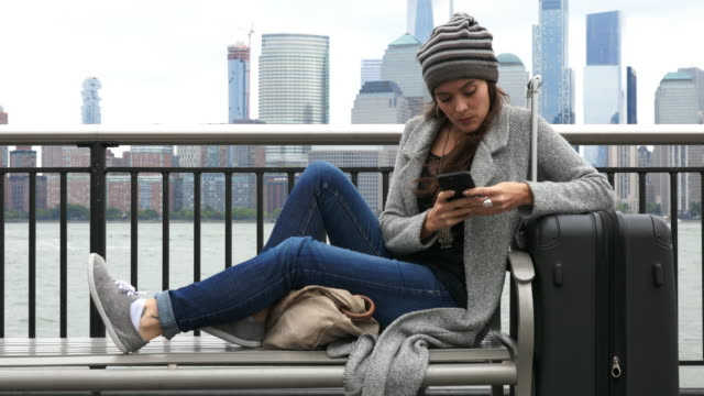 Cinemagraph of Young Woman Traveler Sitting on Bench and Waiting and Using Phone