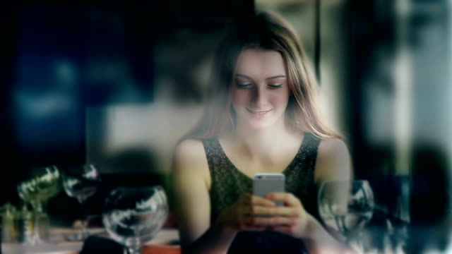 Cinemagraph. Phone message in wine bar. Attractive young woman.