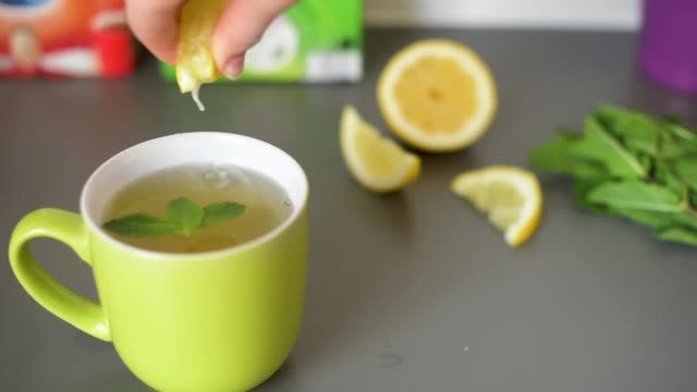 cinemagraph: squeezing lemon into mint tea - 飲み物点の映像素材/bロール