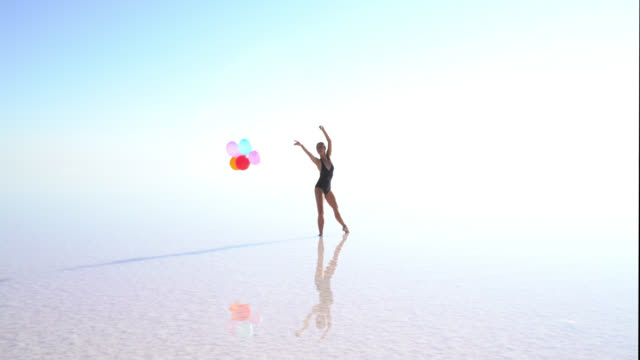 cinemagraph video. young ballerina dancing on the lake with color balloons - cinemagrafia video stock e b–roll