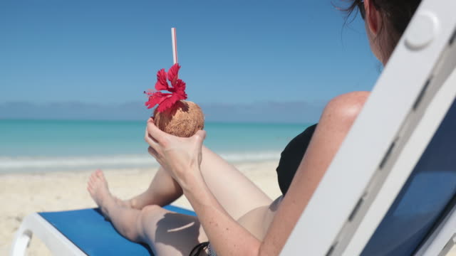 cinemagraph - woman relaxing at beach on chair with drink, cuba - drink stock videos & royalty-free footage