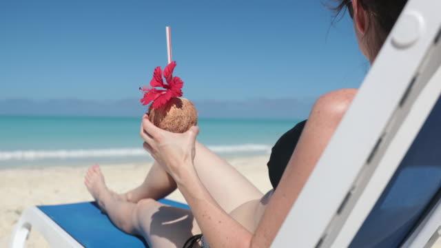 vídeos y material grabado en eventos de stock de cinemagraph - mujer relajante en la playa en silla con bebida, cuba - tumbona