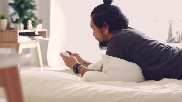 Cinemagraphs : Asian man using smart phone on bed (motion is curtain)