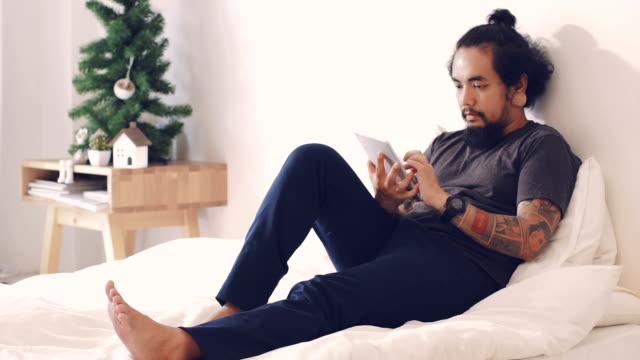 Cinemagramme: Asiatischer Mann mit Tablet auf dem Bett.