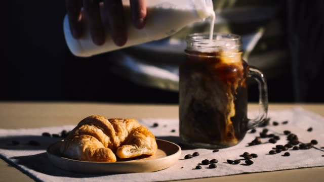 vídeos de stock e filmes b-roll de cinemagraphs : cup of cappuccino cafe and croissant on table - pequeno almoço