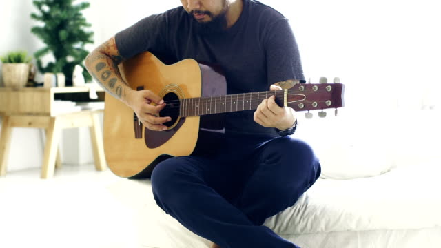 Cinemagraphs : Man playing guitar in living room at home.