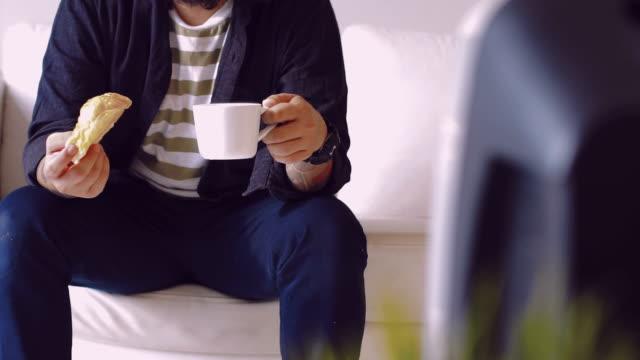 vídeos de stock, filmes e b-roll de cinemagraphs de jovem homem comendo e assistindo tv em casa. - breakfast