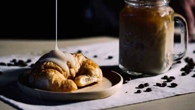 cinemagraphs : pouring milk on croissant with a cup of coffee. - french food stock videos and b-roll footage