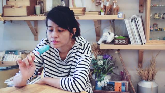 vidéos et rushes de gallery: jeune femme asiatique manger la crème glacée. - cinémagraphie