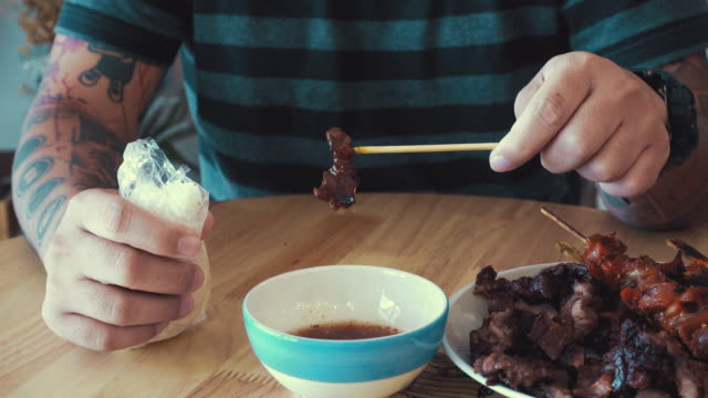 cinemagraphs : young man dipping barbecue sauce. - bbq sauce stock videos and b-roll footage