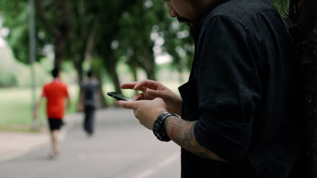 Cinemagraphs : Young man using smartphone at park.