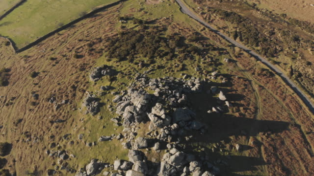 cinematic aerial drone footage of beautiful countryside greenery and natural granite rock formations in dartmoor national park devon uk - granite stock videos & royalty-free footage