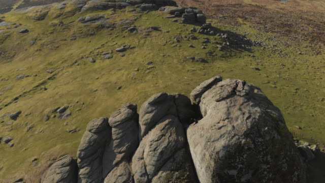cinematic aerial drone footage of haytor rocks and the surrounding beautiful countryside in dartmoor national park devon uk hikers can be seen at the... - geology stock videos & royalty-free footage