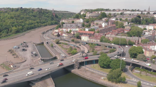 cinematic aerial shot of an overpass running through cumberland basin in bristol's harbourside clifton suspension bridge can be seen in the background - clifton suspension bridge stock videos and b-roll footage