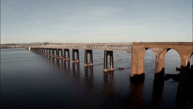 cinematic aerial shot of the tay bridge in dundee during sunrise on a calm morning - スコットランド ダンディー点の映像素材/bロール
