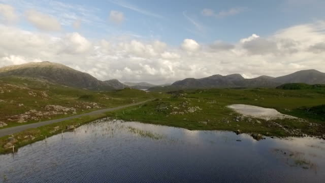 cinematic aerial shot on the isle of harris, scotland near the coast revealing mountains as a van drives past - äußere hebriden stock-videos und b-roll-filmmaterial