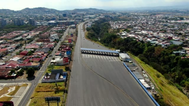 cinematic aerial view of the empty streets near the toll of the road 27 due to the quarentane of covid-19 in costa rica - latin america stock videos & royalty-free footage