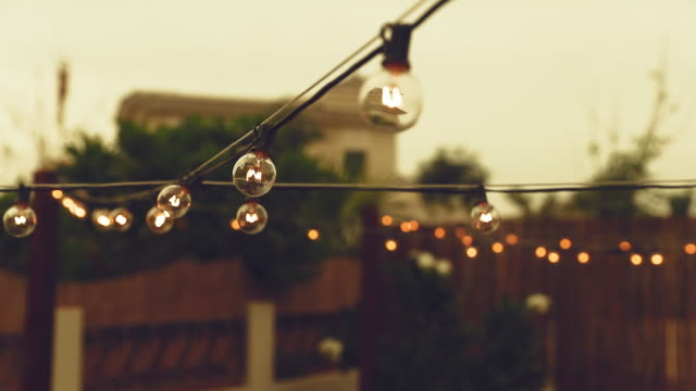 cinematic b-roll from a patio showcasing illuminated string lights - twilight stock videos & royalty-free footage