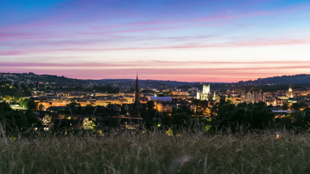 a cinematic day to night timelapse of the british city of bath with a vibrant colourful sky and illuminating buildings street lights - day stock videos & royalty-free footage