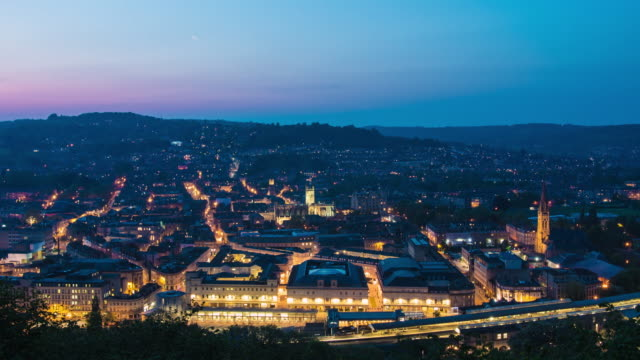 a cinematic day to night timelapse of the british city of bath with a vibrant colourful sky and illuminating buildings street lights - light trail stock videos & royalty-free footage