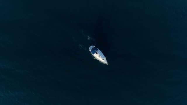 映画のようなドローンの鳥瞰図を明らかに暗い海の水で 1 つの孤独なボート