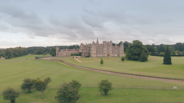 vídeos de stock, filmes e b-roll de a cinematic drone shot of burghley house a grand 16th century english manor house in peterborough - século xvi