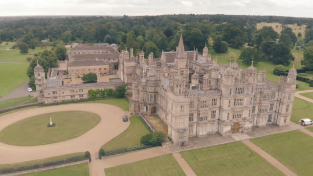 stockvideo's en b-roll-footage met a cinematic drone shot of burghley house a grand 16th century english manor house in peterborough - 16e eeuwse stijl