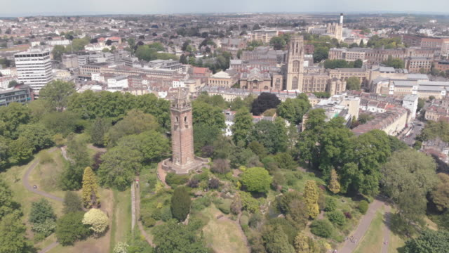 cinematic drone shot of landmark cabot tower in brandon hill park, bristol england. will's memorial university building can be seen in the background. - bristol inghilterra video stock e b–roll