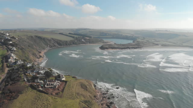 cinematic drone shot of rugged coastline in near bigbury-on-sea in south devon, uk, depicting blue ocean waves, green clifftops and houses - extreme terrain stock videos & royalty-free footage
