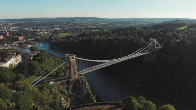cinematic drone shot of the iconic clifton suspension bridge & observatory, surrounding greenery, and city of bristol, uk - bristol inghilterra video stock e b–roll