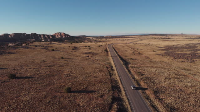 cinematic drone shot of vehicles travelling along a long road in the canyonlands area of utah in the usa. - road trip stock videos & royalty-free footage