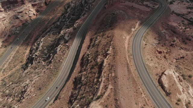 a cinematic drone shot of vehicles travelling along a long road in the canyonlands area of utah in the usa - road trip stock videos & royalty-free footage