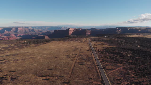 a cinematic drone shot of vehicles travelling along a long road in the canyonlands area of utah in the usa - adventure stock videos & royalty-free footage