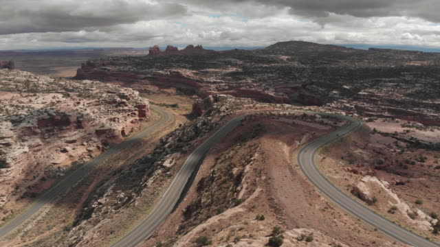 a cinematic drone shot of vehicles travelling along a long road in the canyonlands area of utah in the usa - utah stock videos & royalty-free footage