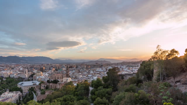cinematic high angle timelapse of the sun setting on the horizon in the spanish city of malaga - mediterranean culture stock videos & royalty-free footage