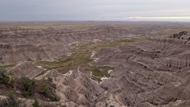 DRONE. Cinematic low level aerial view through green grass revealing Badlands rock formations and canyons