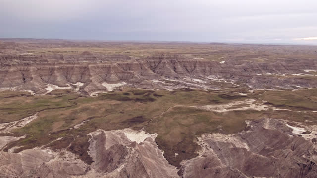 DRONE. Cinematic low level aerial view through tall grass revealing majestic Badlands rock formations and canyons