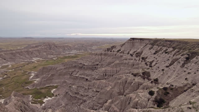 DRONE. Cinematic low level aerial view through tall grass revealing majestic Badlands formations, canyons, and cliff faces