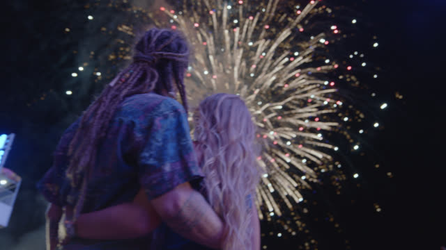 cinematic shot of a beautiful couple kissing under a firework display at a carnival - the americas stock videos & royalty-free footage
