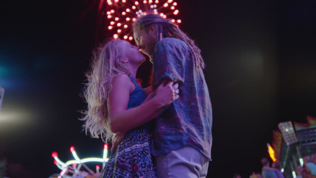 cinematic shot of a beautiful couple kissing under a firework display at a carnival - flirting stock videos & royalty-free footage