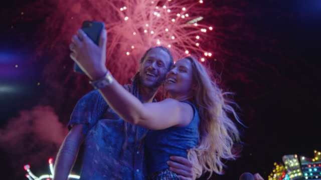 cinematic shot of a beautiful couple taking selfies under a firework display at a carnival - firework display stock videos & royalty-free footage