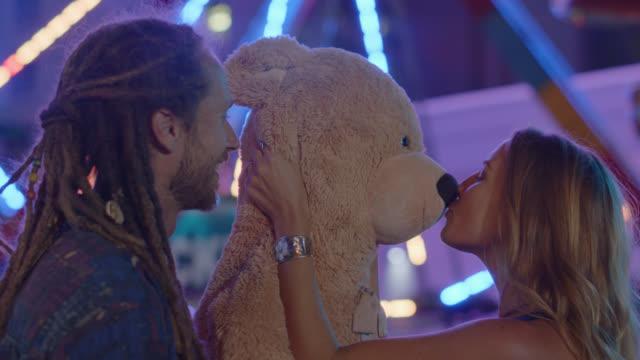 vídeos de stock e filmes b-roll de cinematic shot of a beautiful woman kissing giant teddy bear and boyfriend at a carnival - carnaval evento de celebração